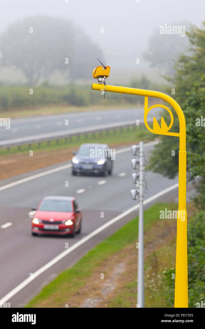Drivers passing beneath a brightly coloured yellow average speed trap camera along the A55 near Rhuallt Hill, Denbighshire - Stock Image