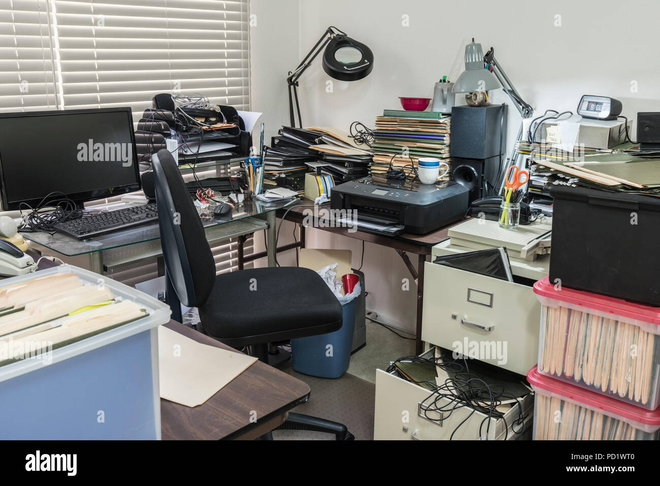 Messy business office desk with boxes of files and disorganized clutter. - Stock Image