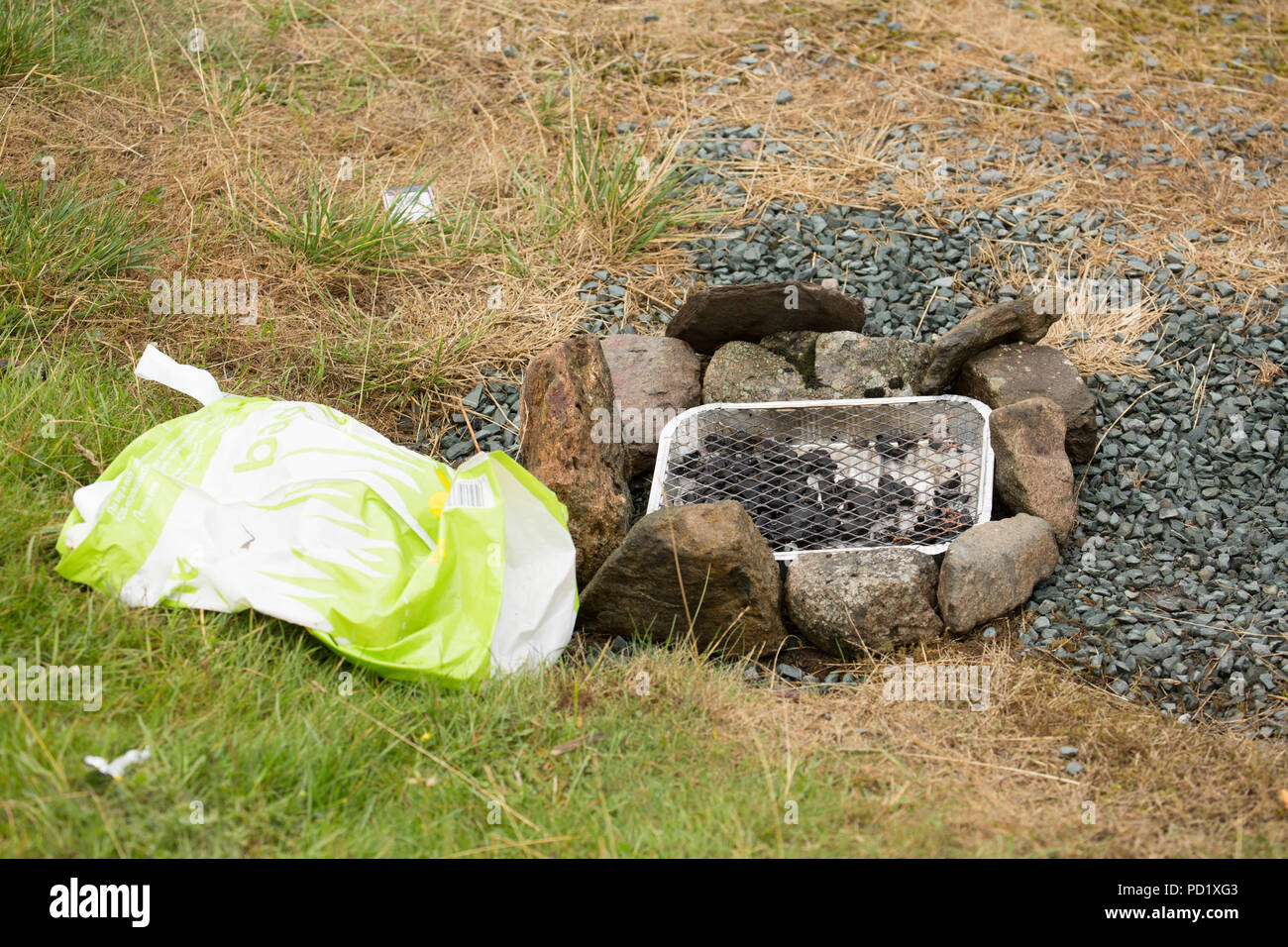A disposable barbecue and supermarket carrier bag left beside a car park next to the Kirkstone Pass in The Lake District Cumbria England UK GB. - Stock Image