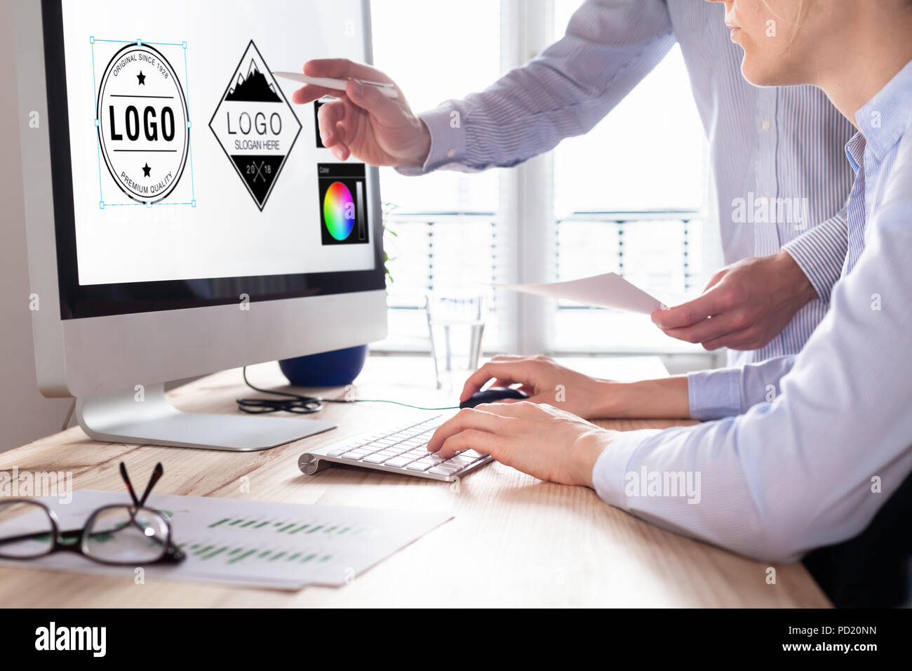 Designer team sketching a logo in digital design studio on computer, creative graphic drawing skills for marketing and branding - Stock Image
