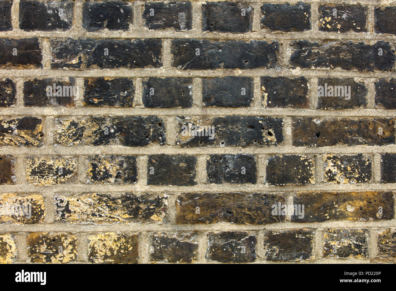 Heritage free standing wall in Hampstead, London, with old London weathered yellow bricks in English bond - Stock Image