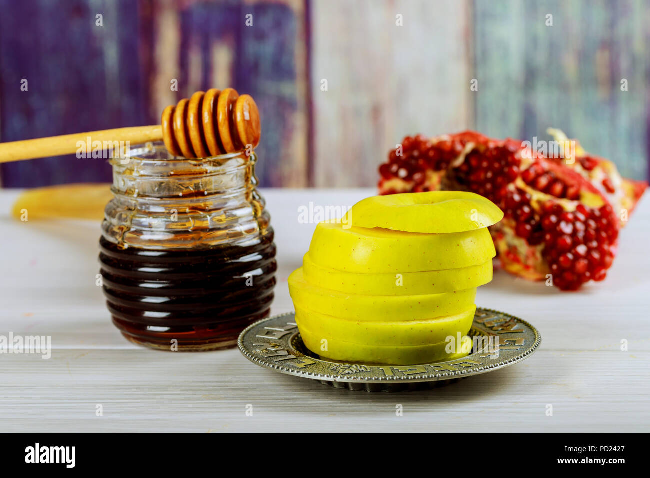 rosh hashanah jewesh holiday concept - shofar, torah book, honey, apple and pomegranate over wooden table. traditional holiday symbols. - Stock Image