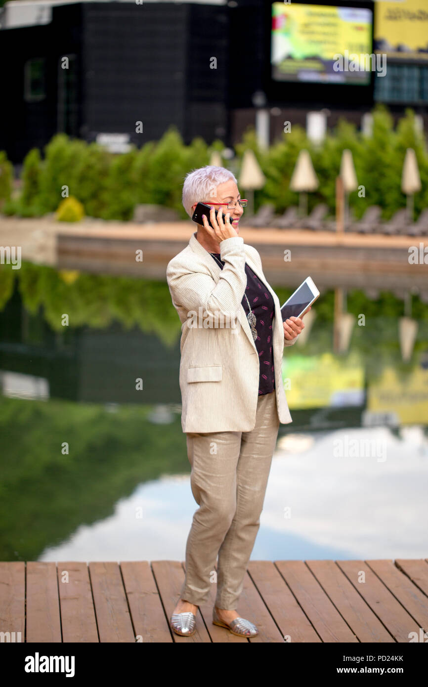full length portrait of positive mature woman making a phone call in the resort - Stock Image