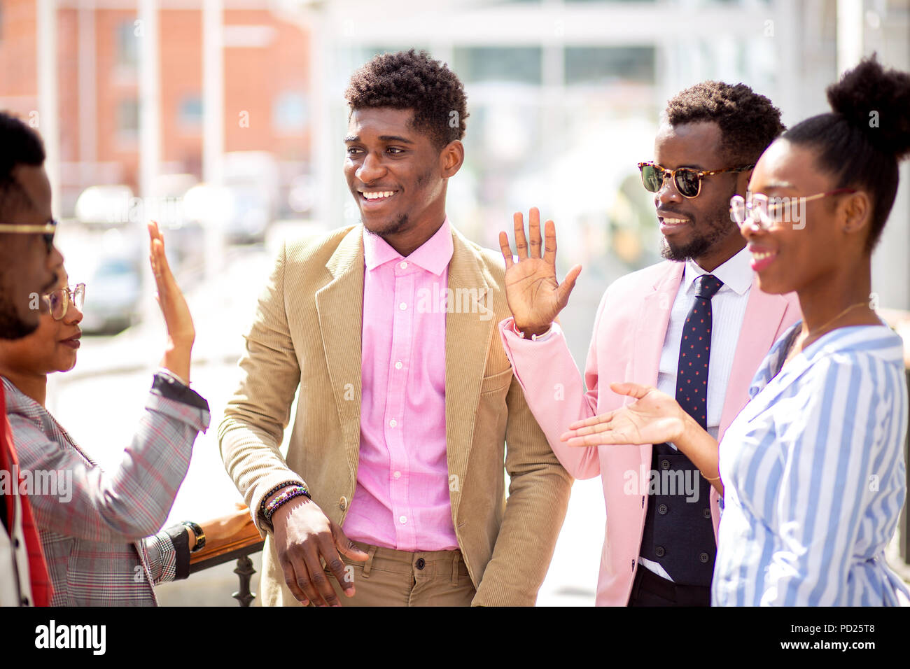 fasion students are giving high five in the street beacause they