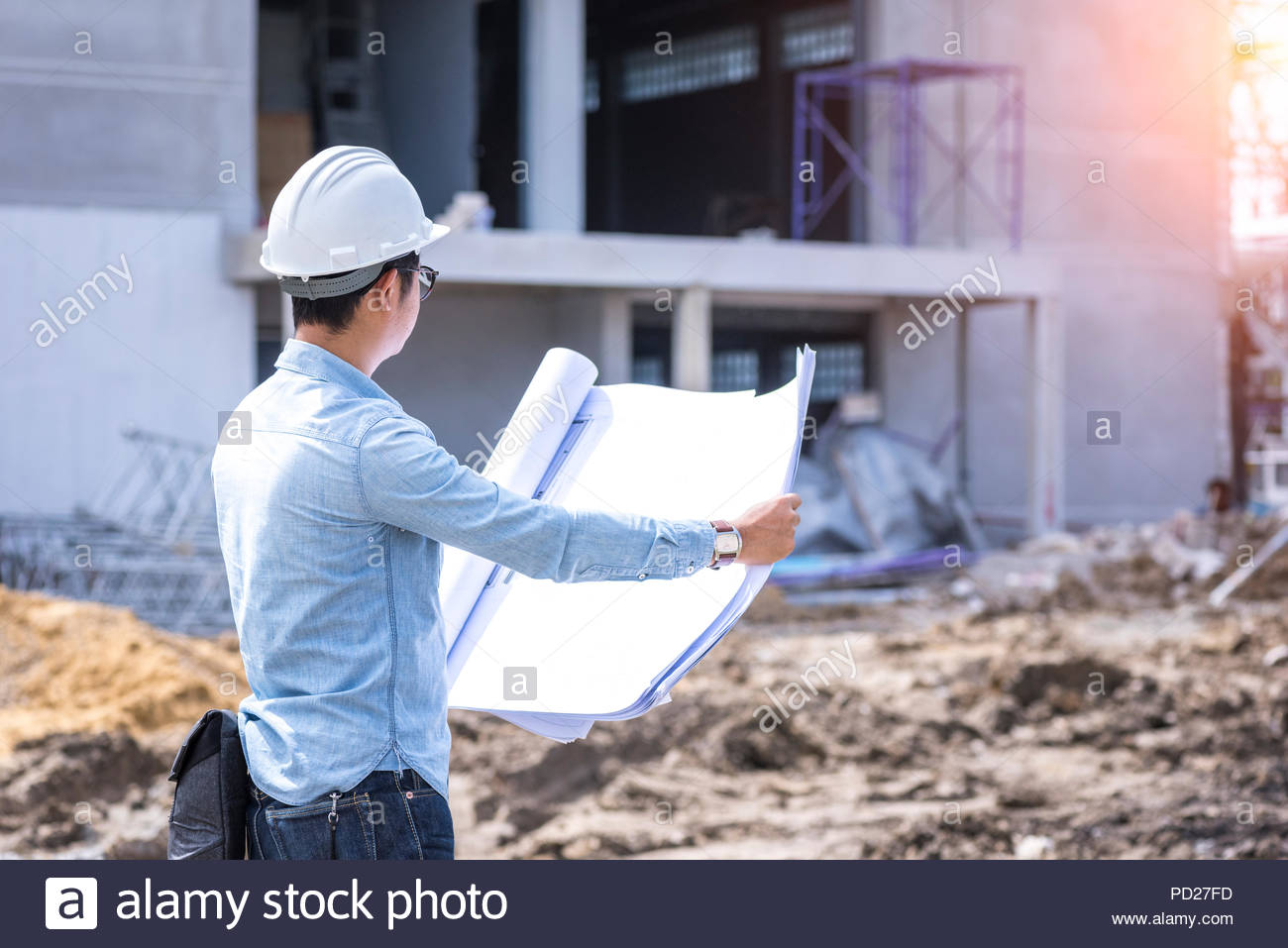 civil engineer working with blueprint for project quality control at construction site - Stock Image