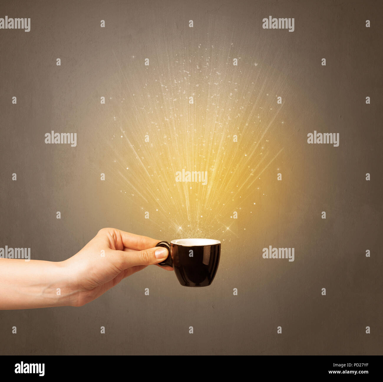 Young female hand holding coffee cup with a beam of light rising out of it  - Stock Image