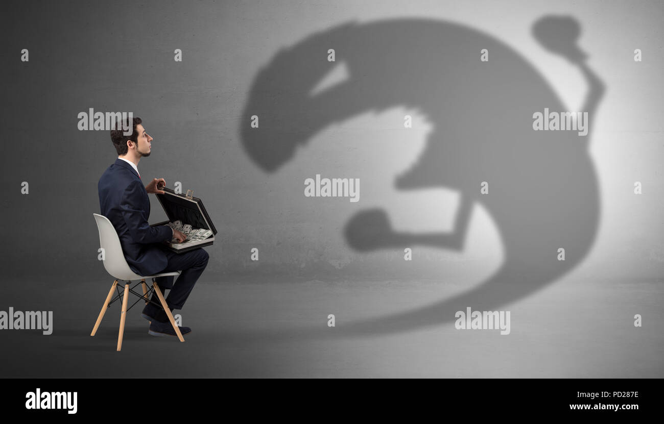 young businessman staying and negotiate with a monster shadow stock