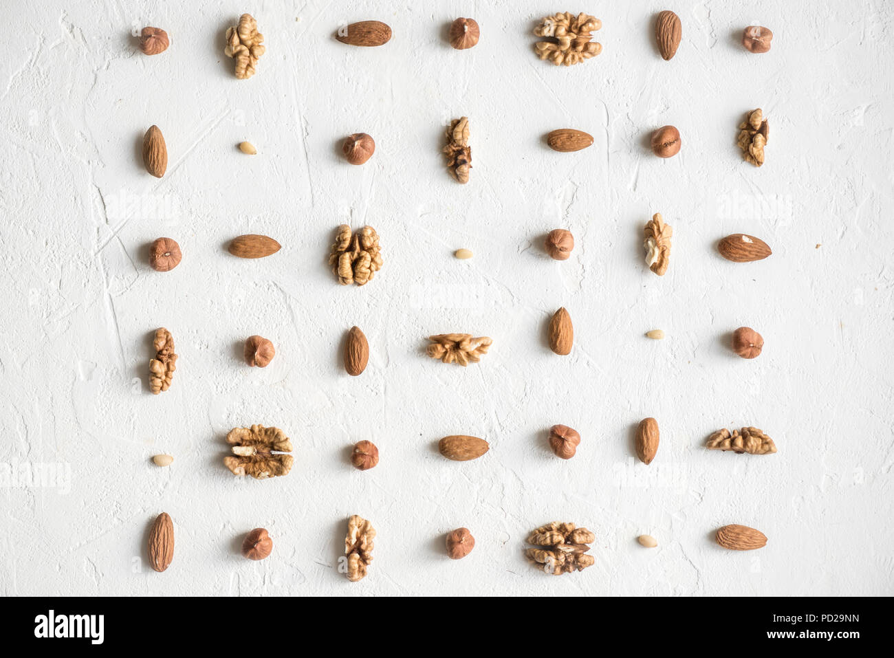 Various nuts (walnuts, hazelnuts, almonds and pine nuts) repetition on white background as pattern, flat lay with copy space. - Stock Image