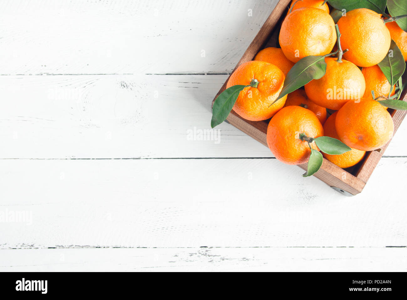 Tangerines (oranges, clementines, citrus fruits) with green leaves over white wooden background with copy space - Stock Image