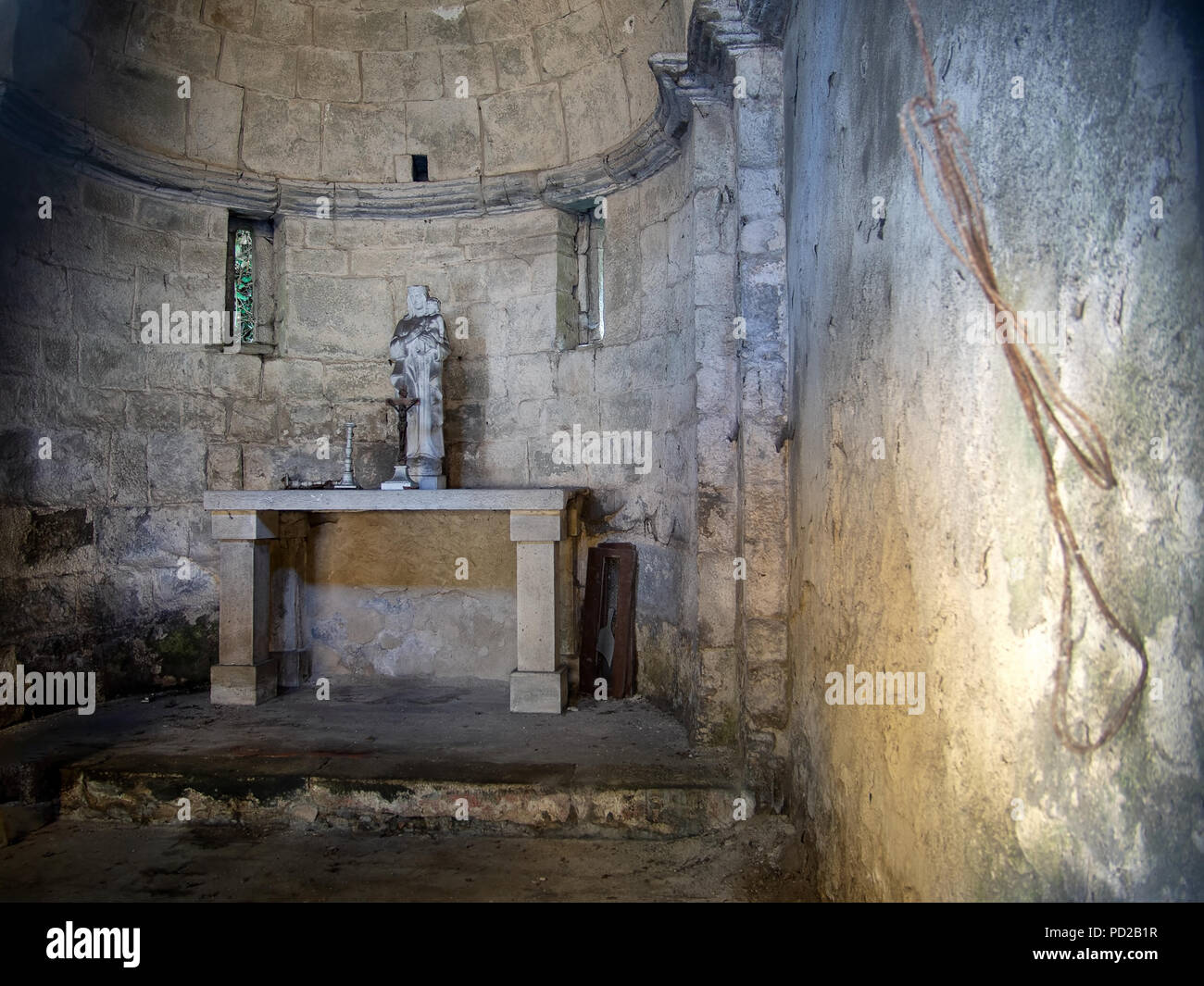 The interior of an ancient, small and forgotten church. Lunigiana, Italy. With statue and crucifix. - Stock Image