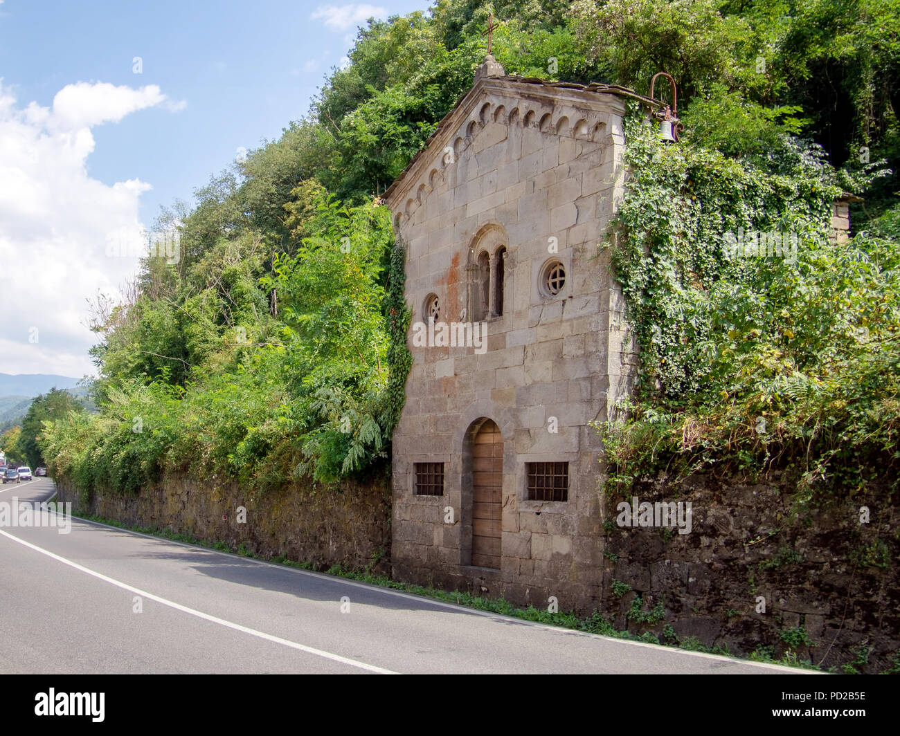 Ancient small Catholic church, closed, neglected and overgrown. Lunigiana, Italy. - Stock Image