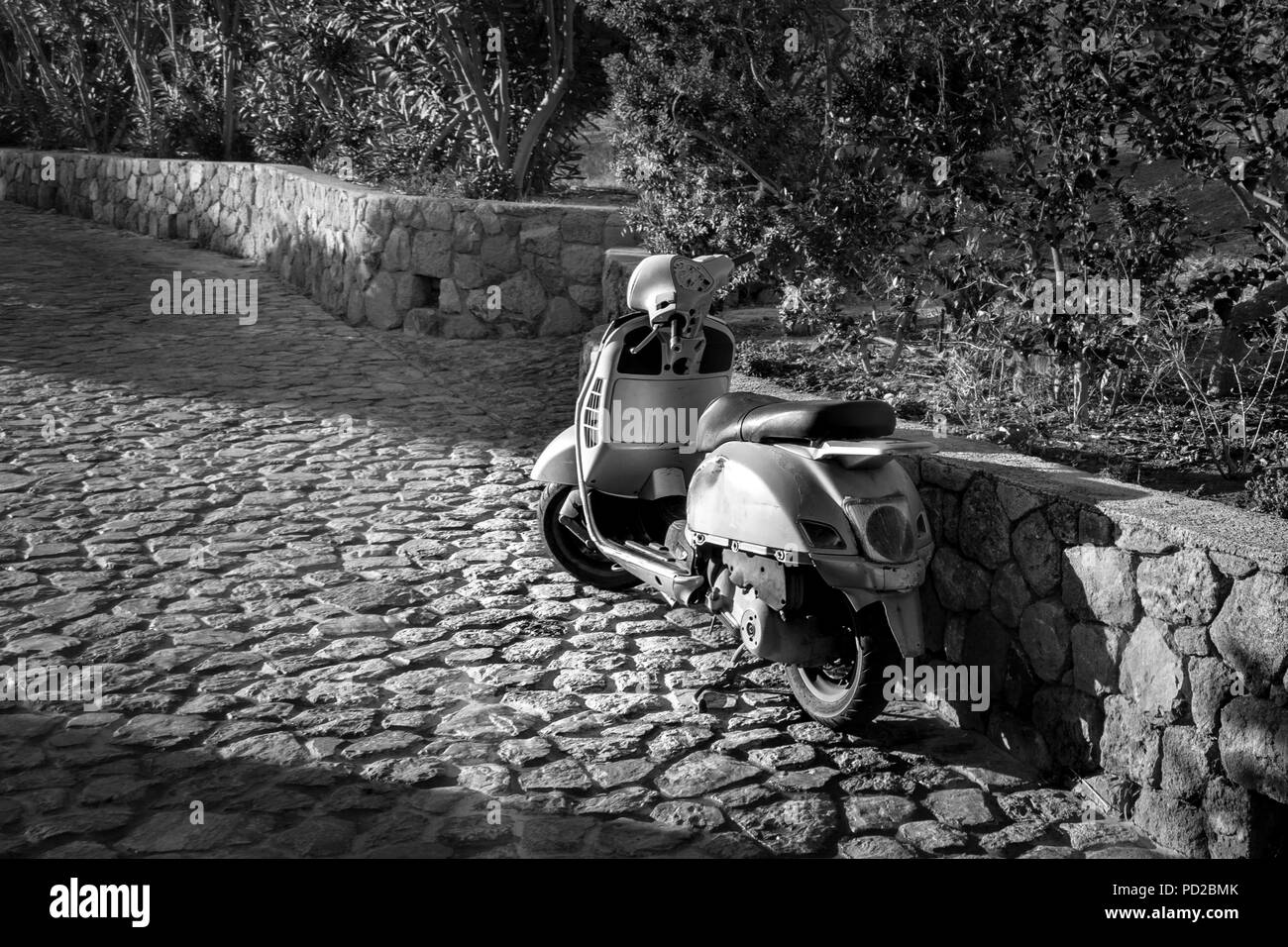 This is a black and white photograph of a moped parked on a cobblestone road.  the morning sun is shining onto the scooter. - Stock Image