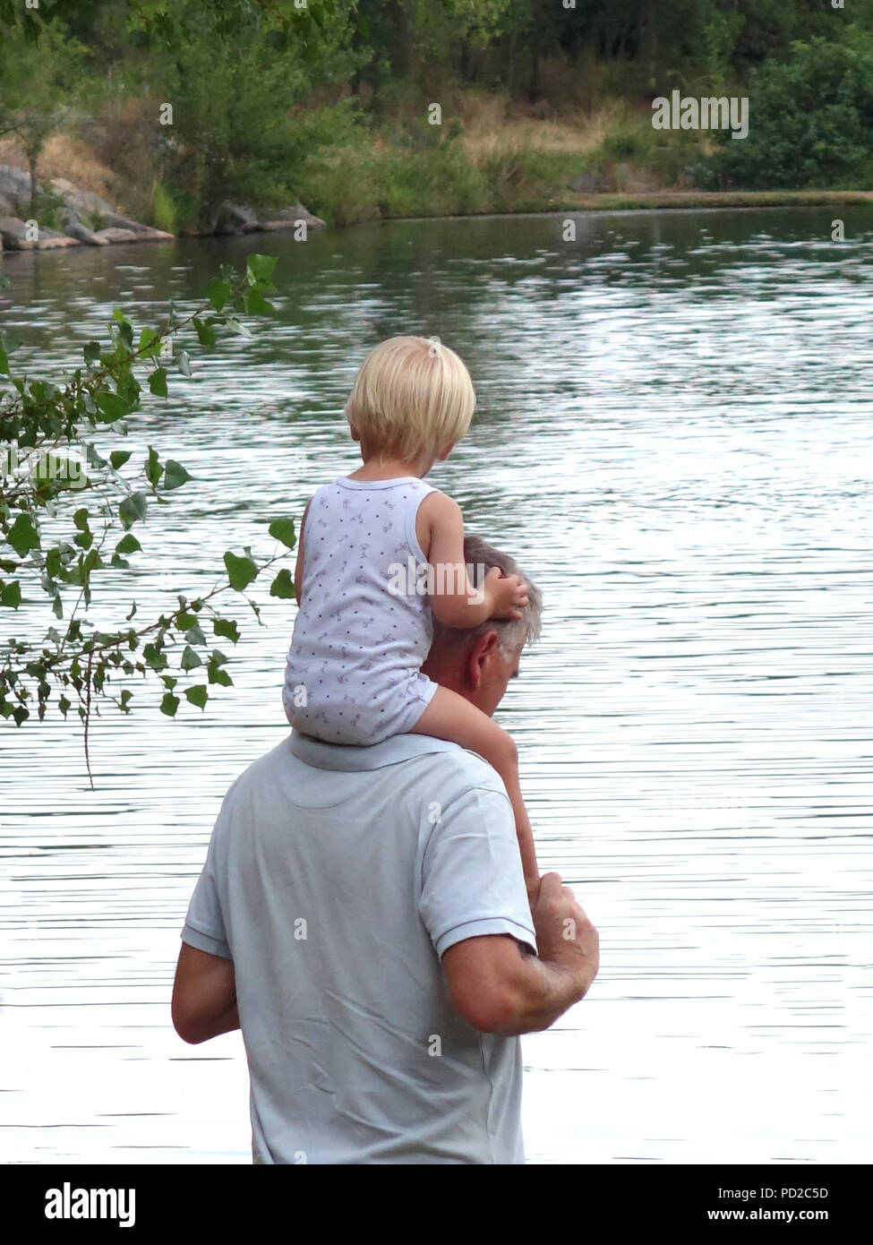 Small child on adult males shoulders walking by a lake - Stock Image