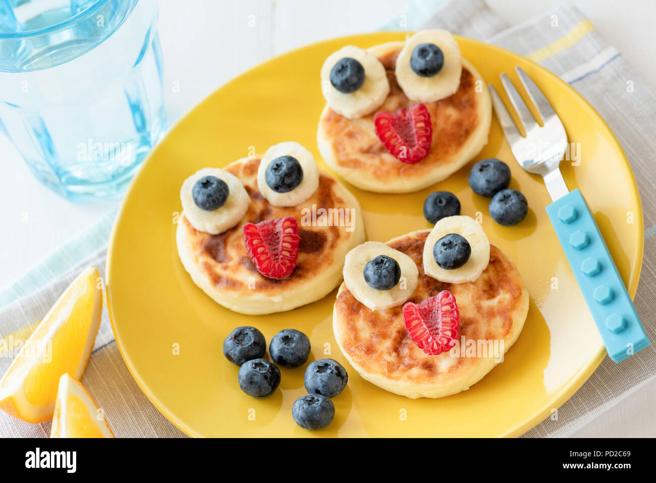 Fun food for kids. Pancakes with funny animal faces on colorful yellow plate. Kids meal. Selective focus Stock Photo