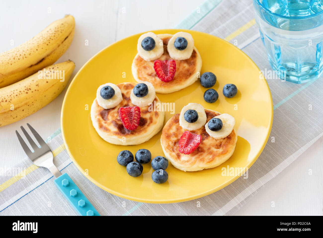 Fun food for kids. Pancakes with funny animal faces on colorful yellow plate. Kids meal. Selective focus - Stock Image