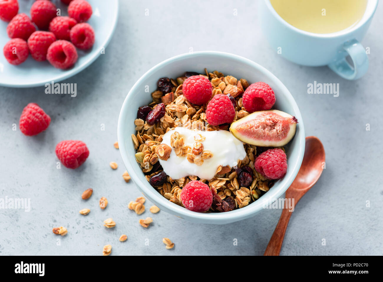 Healthy Breakfast Granola Bowl With Yogurt, Berries and Cup of Green Tea on Concrete Background. Top view. Concept of healthy eating, Healthy lifestyl - Stock Image