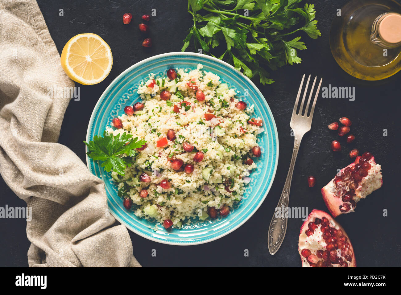 Middle Eastern Salad Tabbouleh With CousCous, Pomegranate seeds, Parsley. Top view, toned image - Stock Image