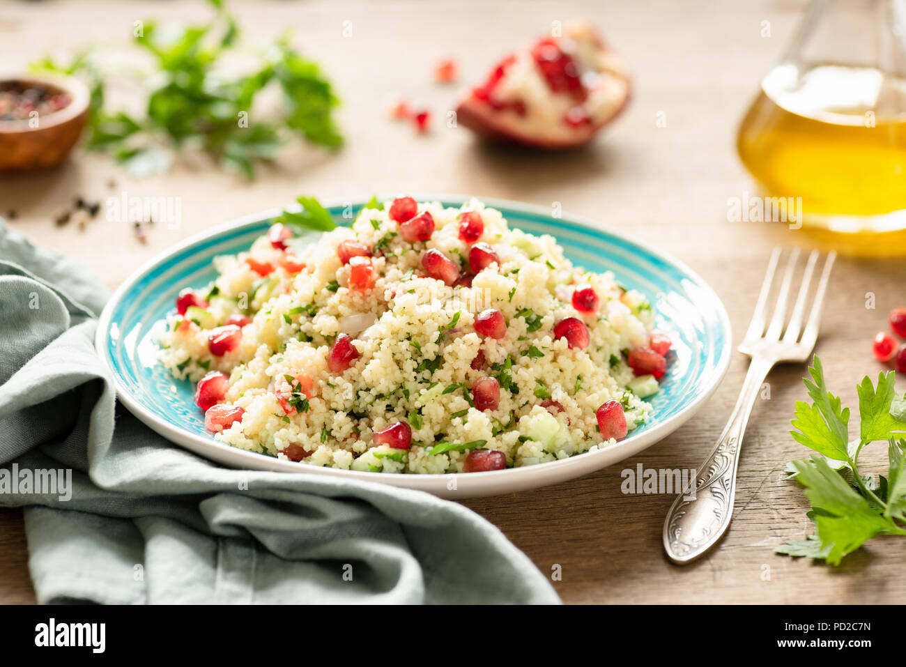 Tabbouleh, Middle Eastern couscous salad with pomegranate, parsley, cucumber on authentic turquoise plate. Vegetarian meal - Stock Image