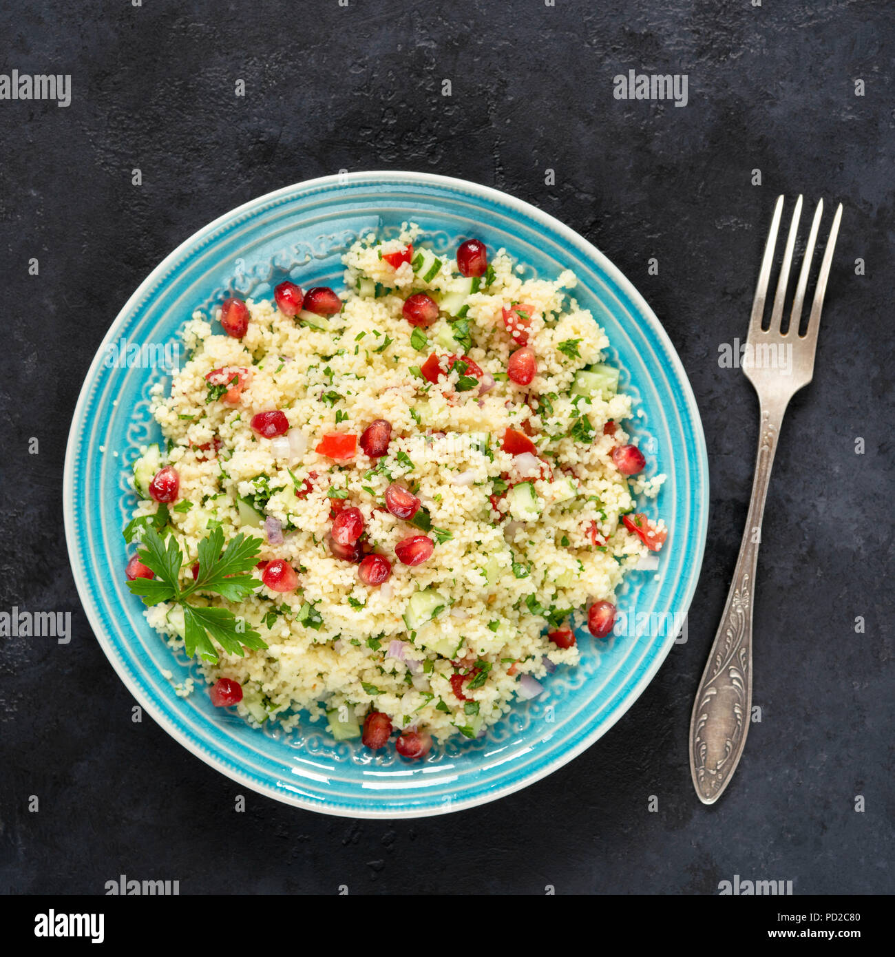 Tabbouleh salad with couscous and pomegranate seeds on a blue plate on black stone. Top view, square crop - Stock Image