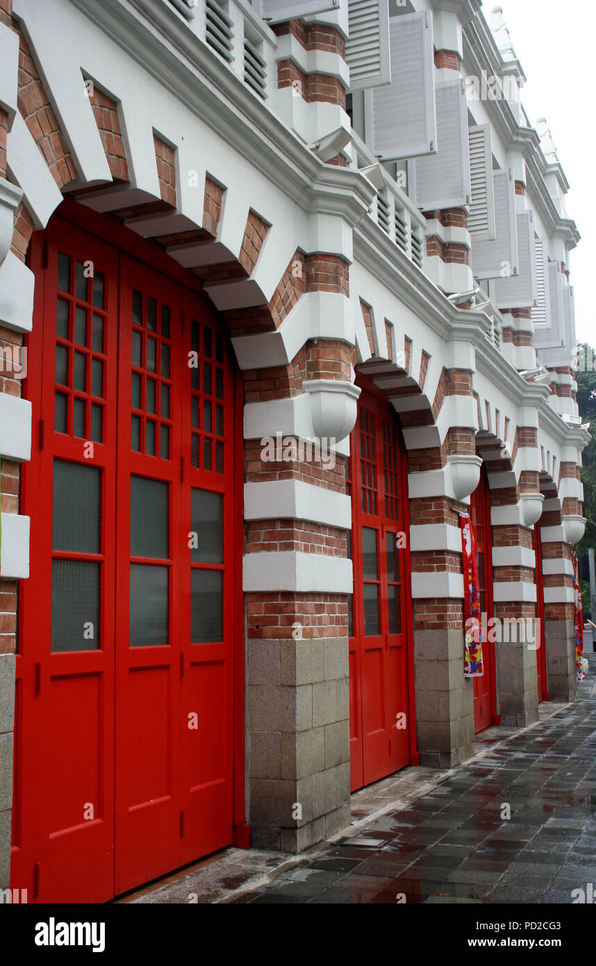 Heritage Building with Large Red Doors in a Row and White Window Shutters, Singapore - Stock Image