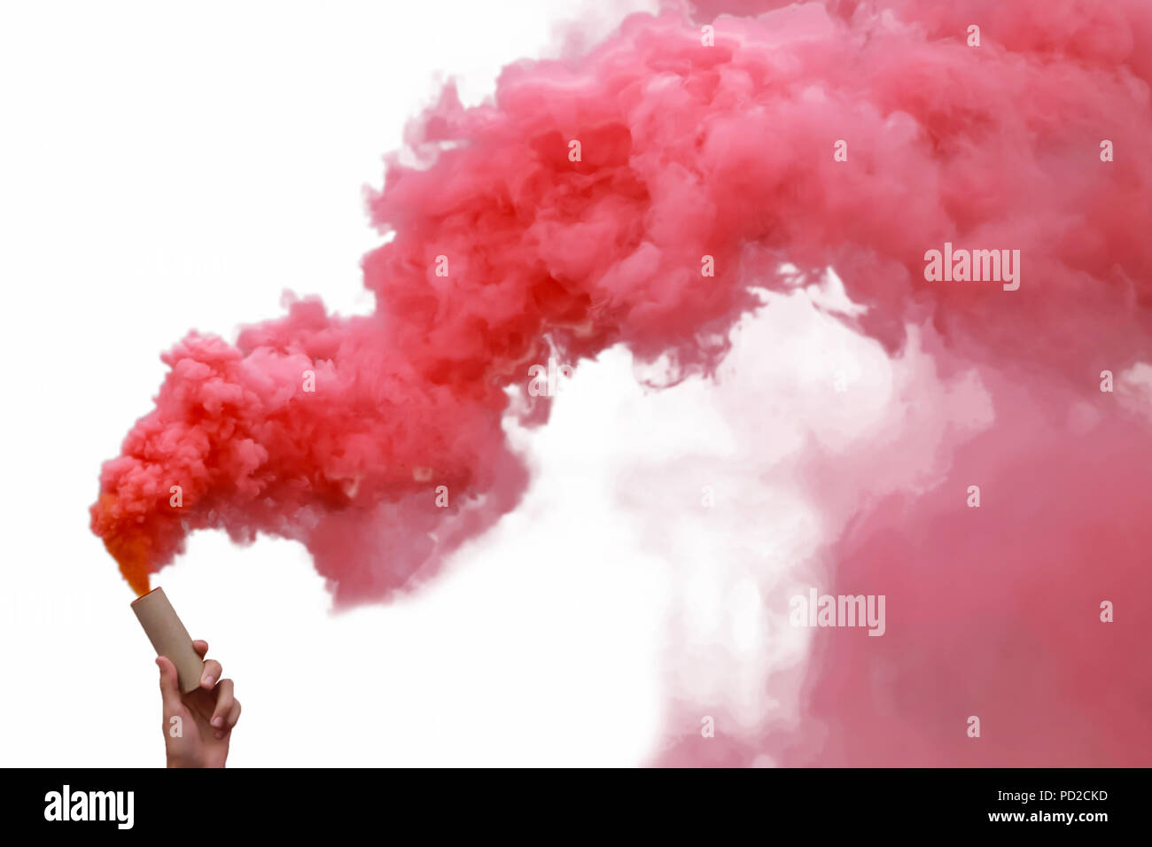 Human hand holding smoke bombs with red smoke, isolated on white background. - Stock Image