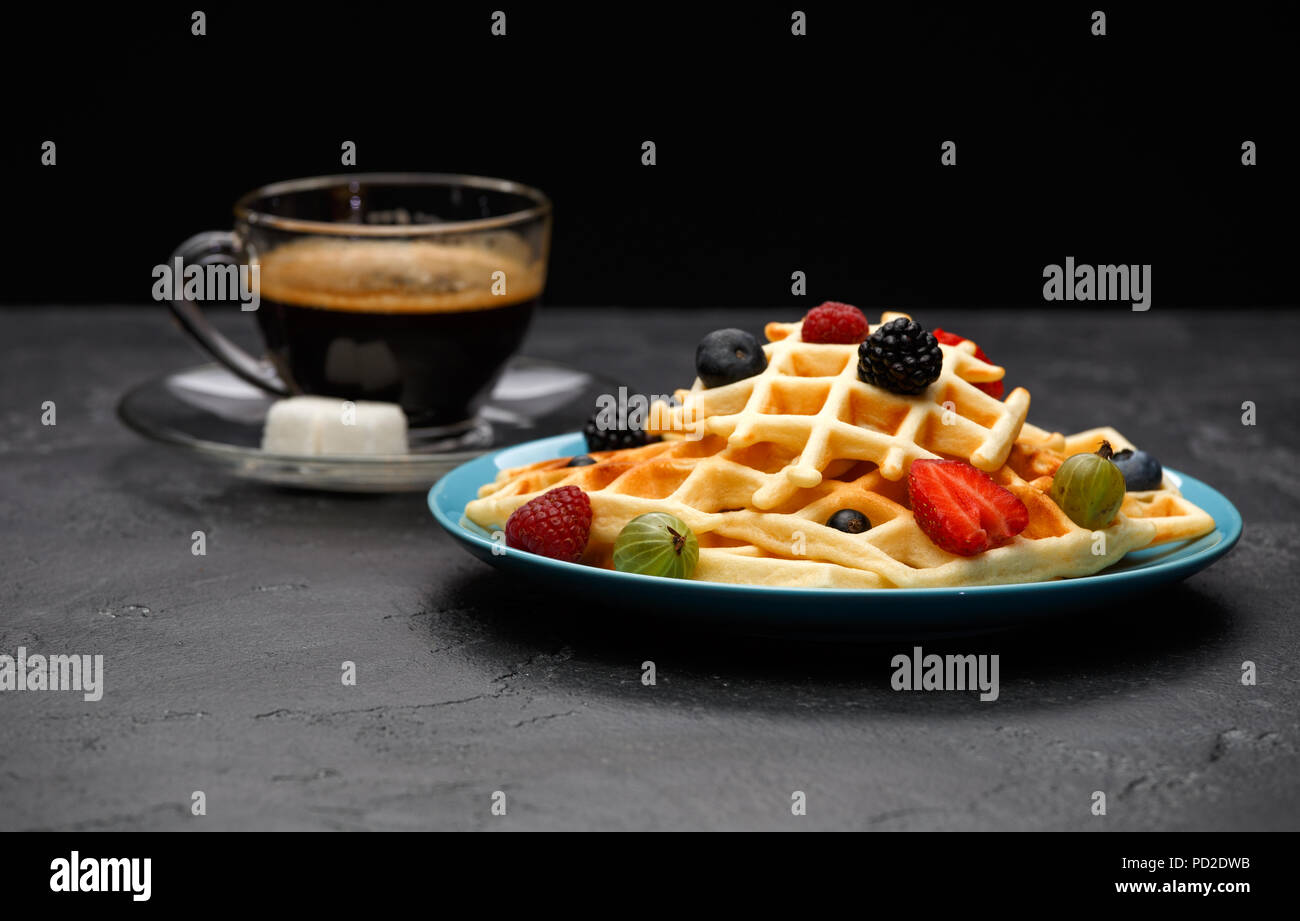 Photo of cup of black coffee with sugar with Viennese waffles with strawberries, raspberries - Stock Image
