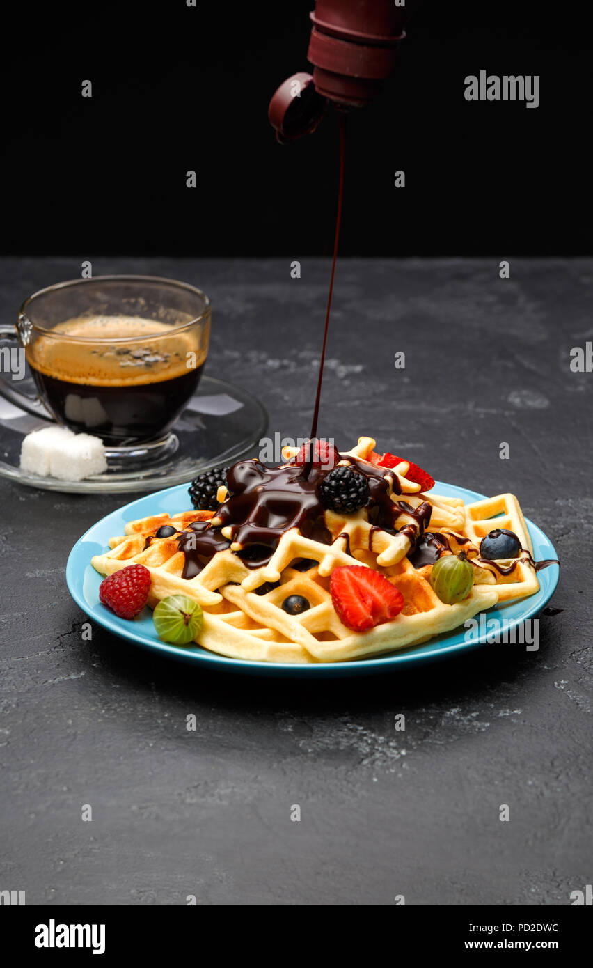 Photo of cup of black coffee with sugar with Viennese waffles with strawberries, raspberries, gooseberries and chocolate Stock Photo
