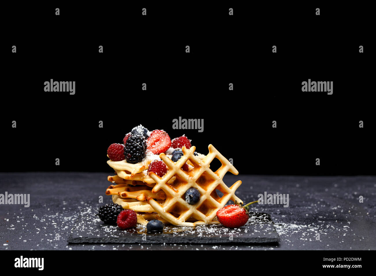 Photo of viennese wafers with fresh raspberries, strawberries sprinkled with powdered sugar on blackboard against blank background - Stock Image