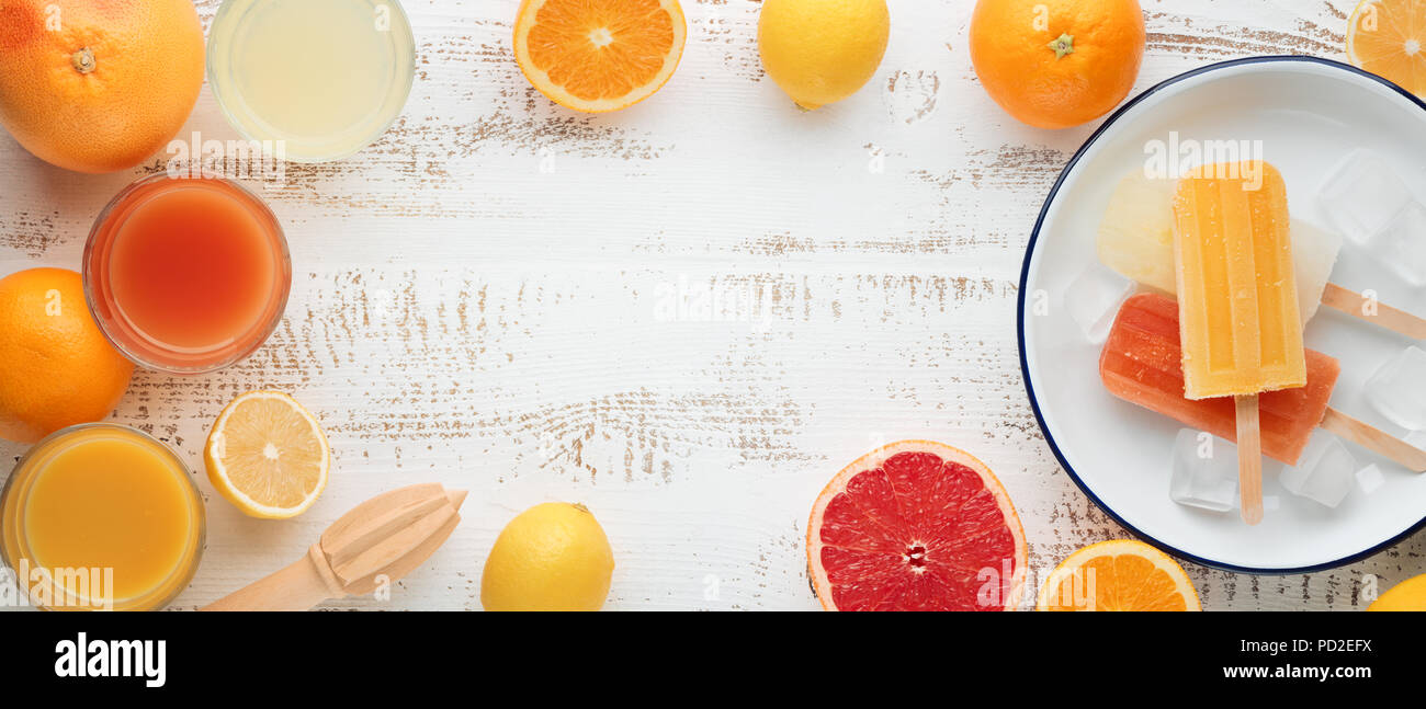 Homemade orange and lemon popsicles and citrus fruits on stone black background. Summer food concept. - Stock Image