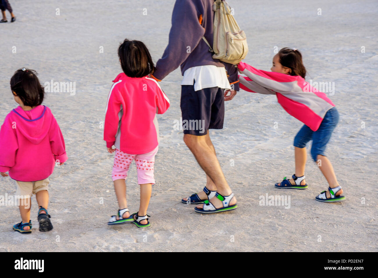 Miami Beach Florida Asian man girl girls father daughters parent child sisters family tugging pulling holding hands walking beha - Stock Image