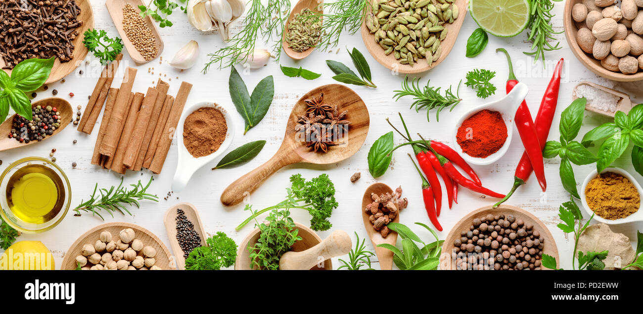 Various herbs and spices. Flat lay of spices ingredients chilli ,pepper, garlic,dries thyme, cinnamon,star anise, nutmeg,rosemary, sweet basil and kaf - Stock Image