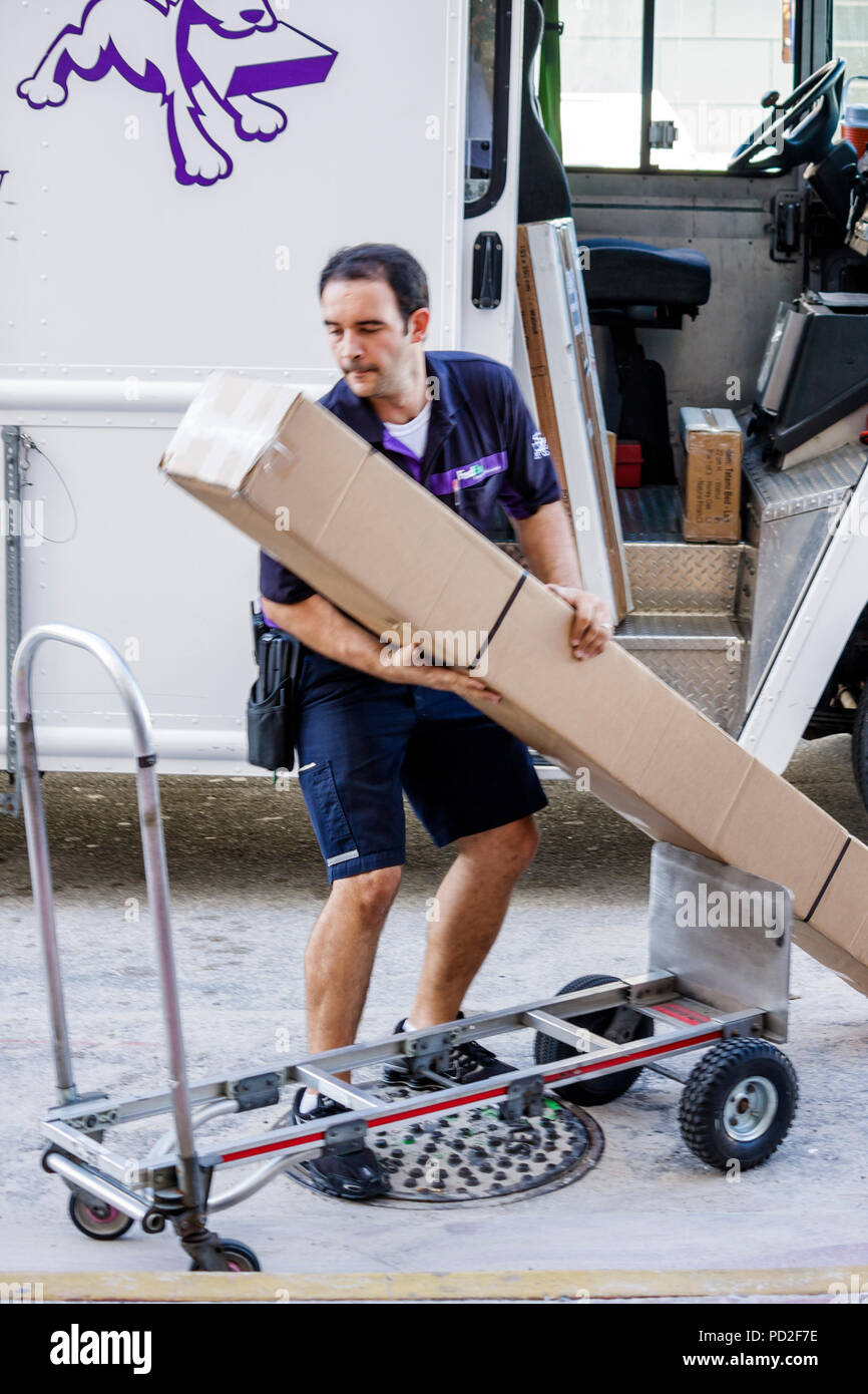 Miami Beach Florida FedEx worldwide company business shipping Hispanic man worker courier truck driver dolly cart lifting box pa - Stock Image