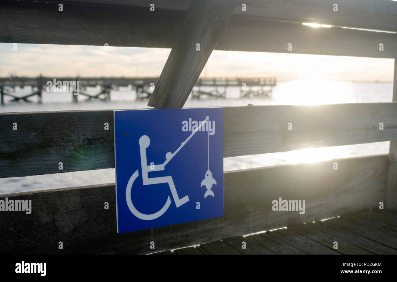 Blue sign indicates wheelchair accessible on fishing pier - Stock Image