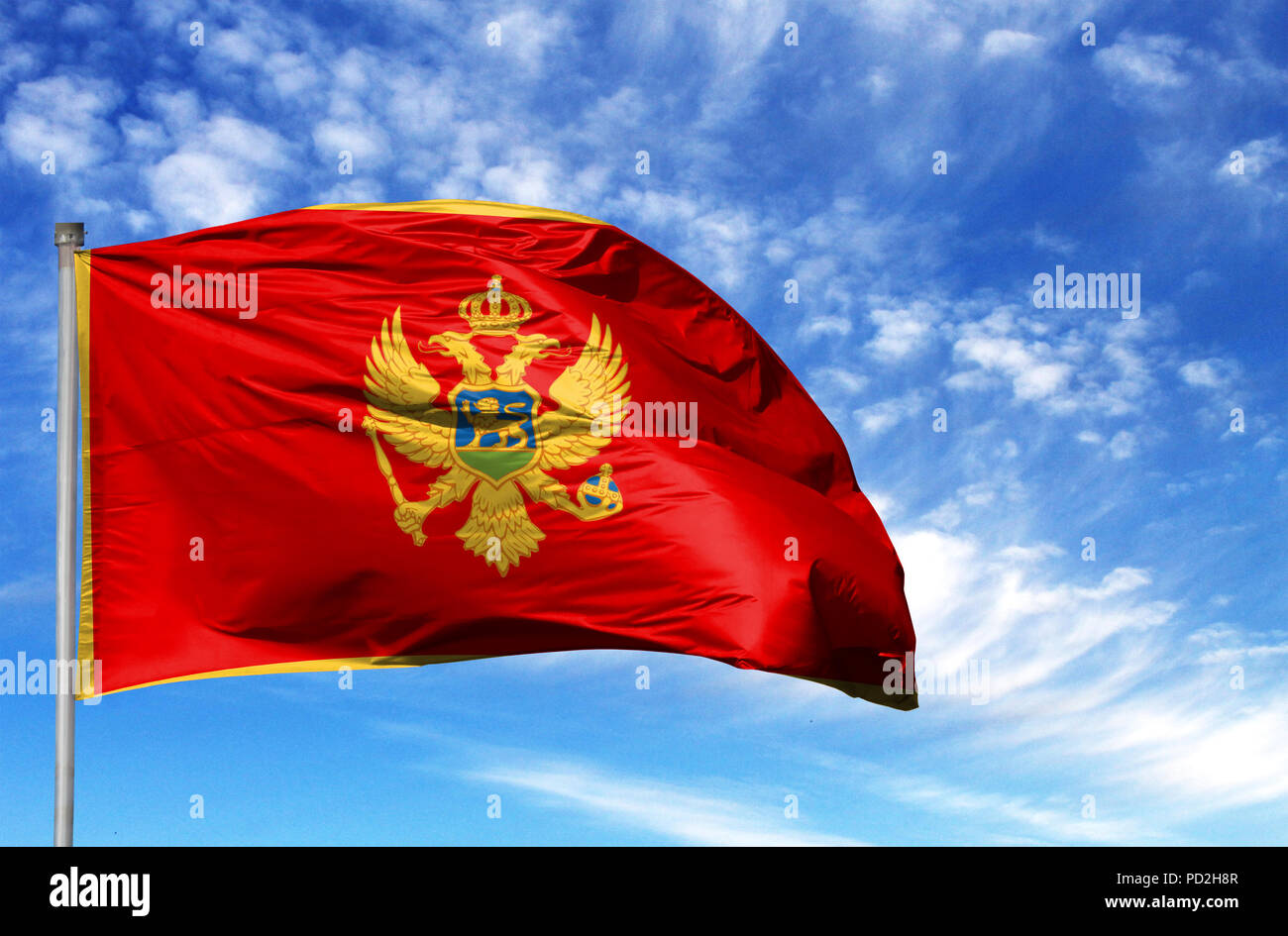 National flag of Montenegro on a flagpole in front of blue sky. Stock Photo
