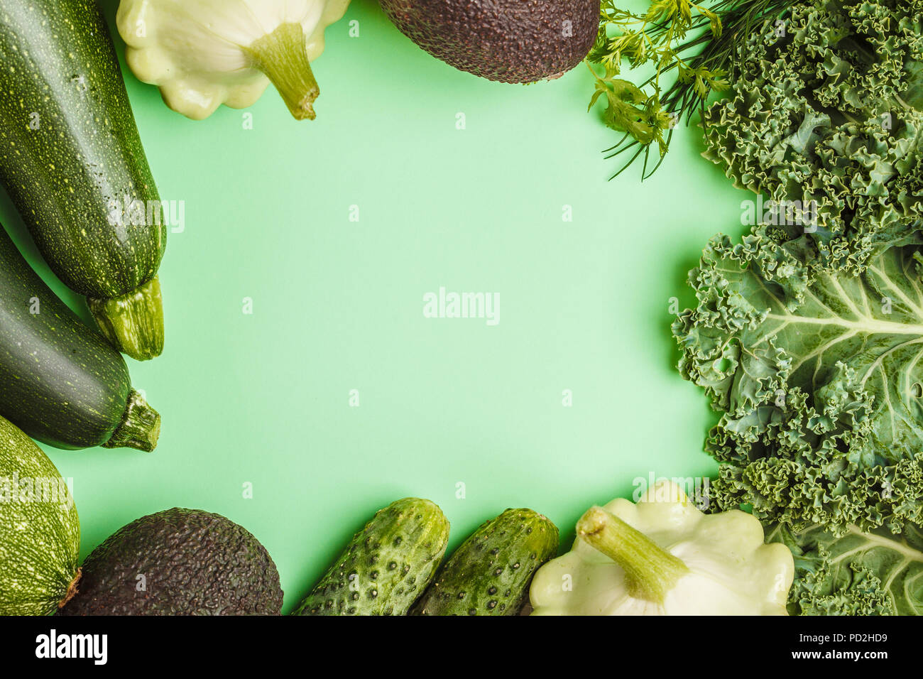 Assortment of green vegetables on green background, top view. Fruits and vegetables containing chlorophyll. - Stock Image