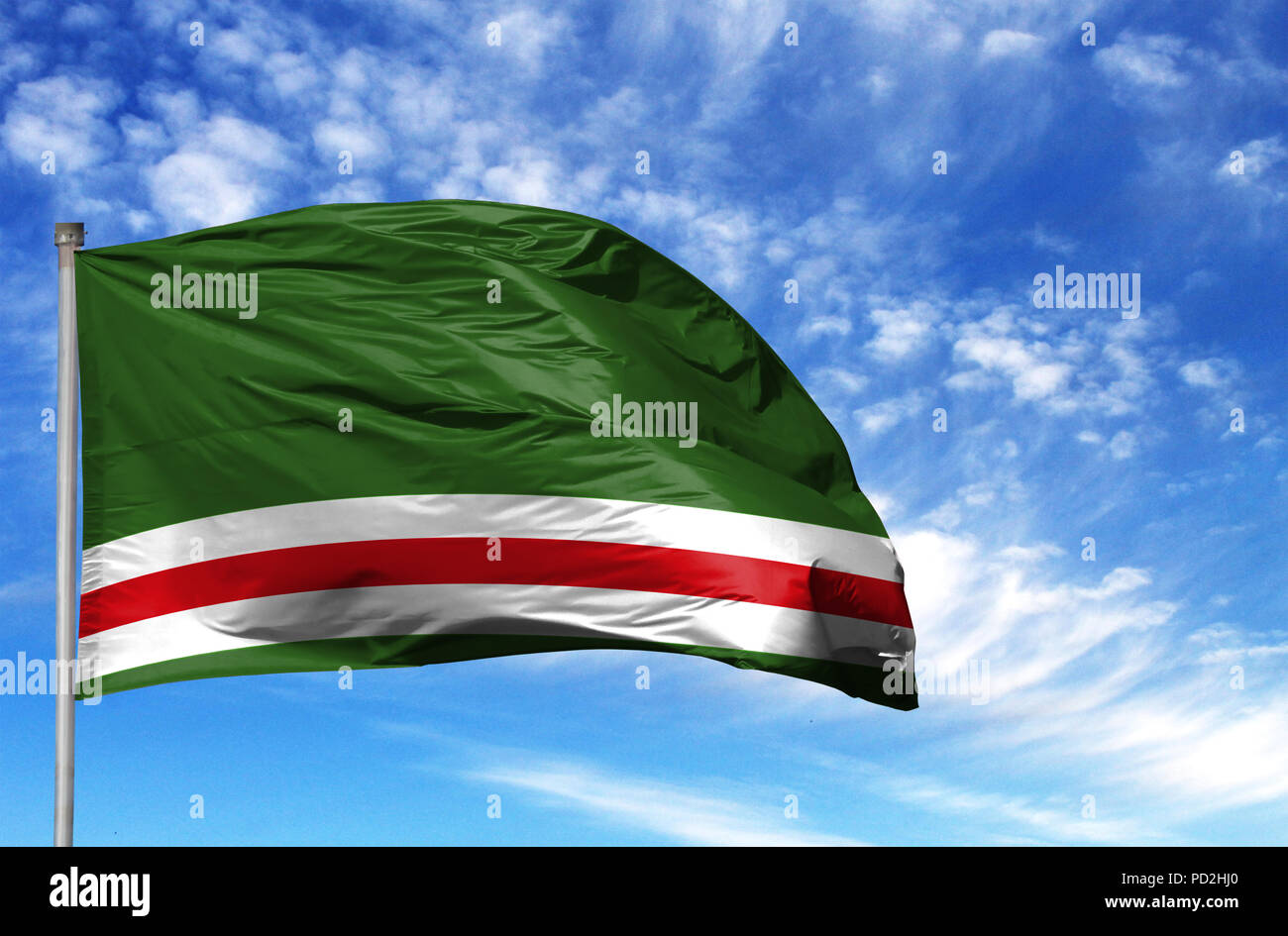 National flag of Chechen Republic of Ichkeria on a flagpole in front of blue sky. - Stock Image