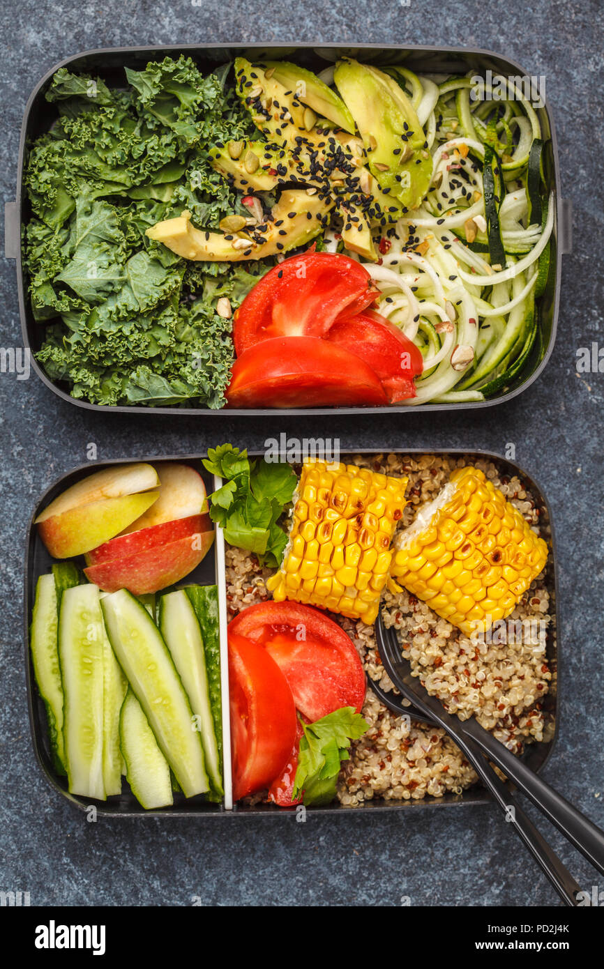 Healthy meal prep containers with quinoa, avocado, corn, zucchini noodles and kale. Takeaway food. Dark background, top view. - Stock Image