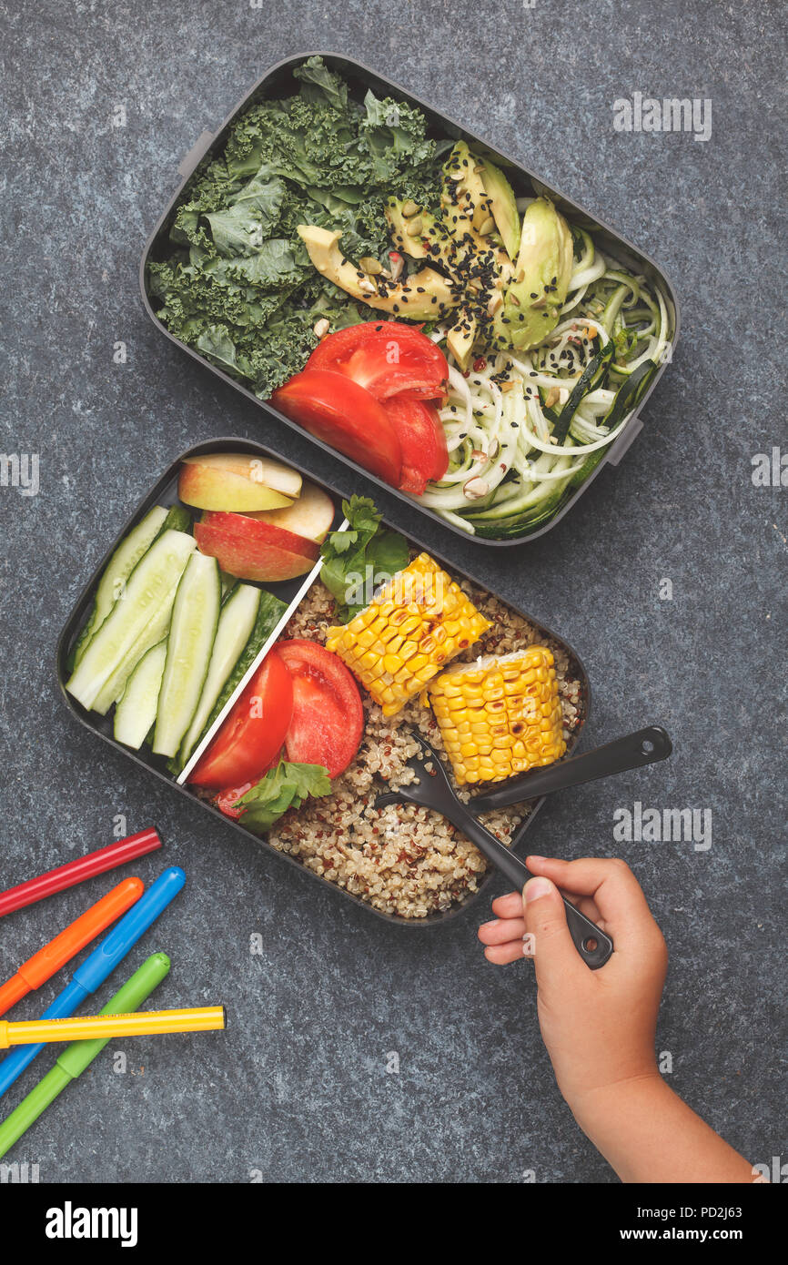 Healthy meal prep containers with quinoa, avocado, corn, zucchini noodles and kale. Takeaway food at school. Dark background, top view. - Stock Image