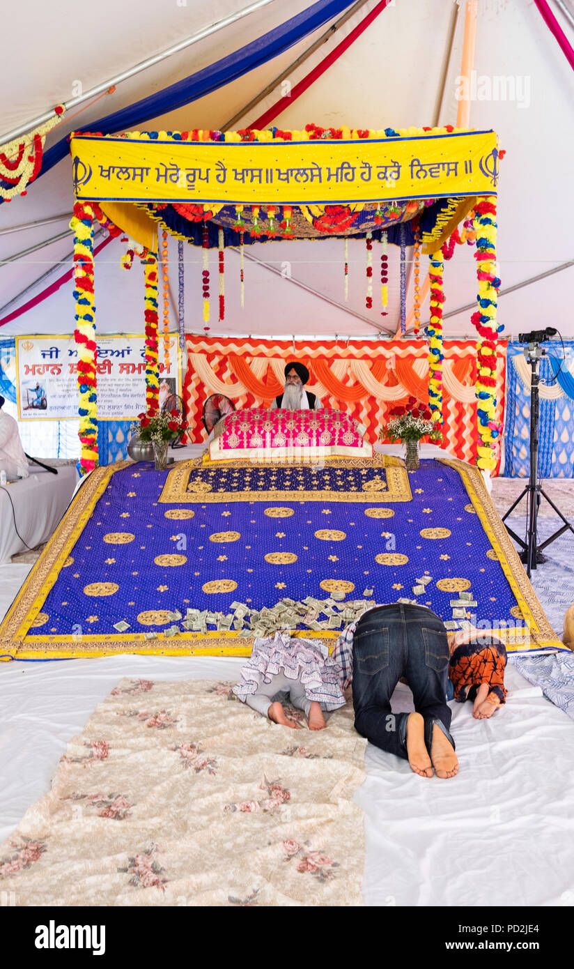 A father and 2 children bowing in prayer at an outdoor Sikh prayer session in a tent in Smokey Park, Richmond Hill, Queens, New York - Stock Image