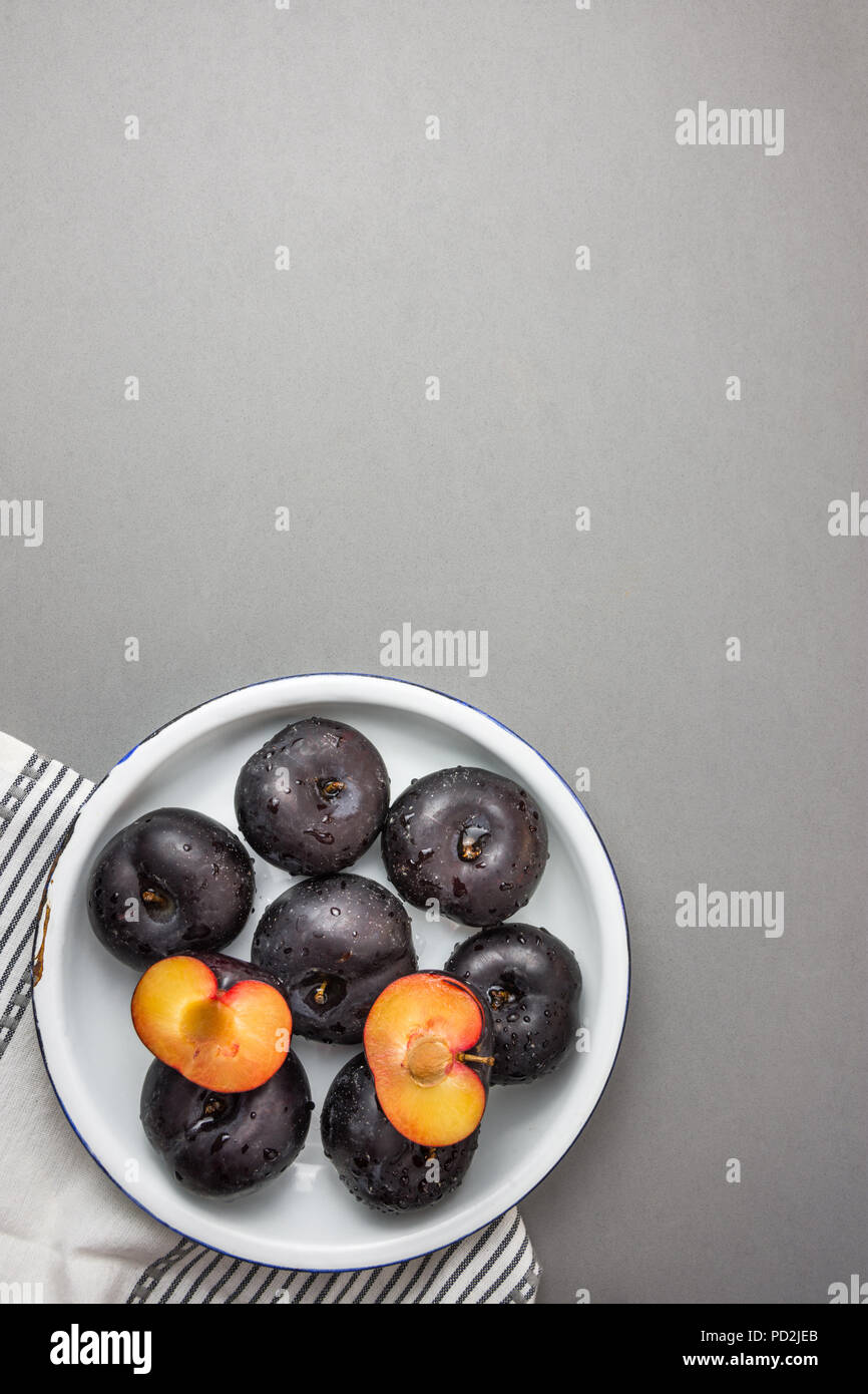 Dark red big plums whole and halved on white vintage enamel plate. White cotton towel on gray stone background. Minimalist style. Autumn fall harvest. - Stock Image