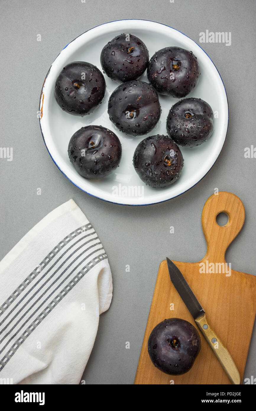Dark red big plums on white vintage enamel plate. Wooden cutting board knife white cotton towel on gray stone background. Minimalist style. Autumn fal - Stock Image