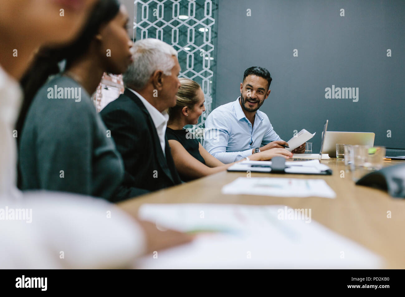 Positive young man with team of multi-ethnic people discussing productive strategy in boardroom. Executive reads a report for the business team in mee - Stock Image