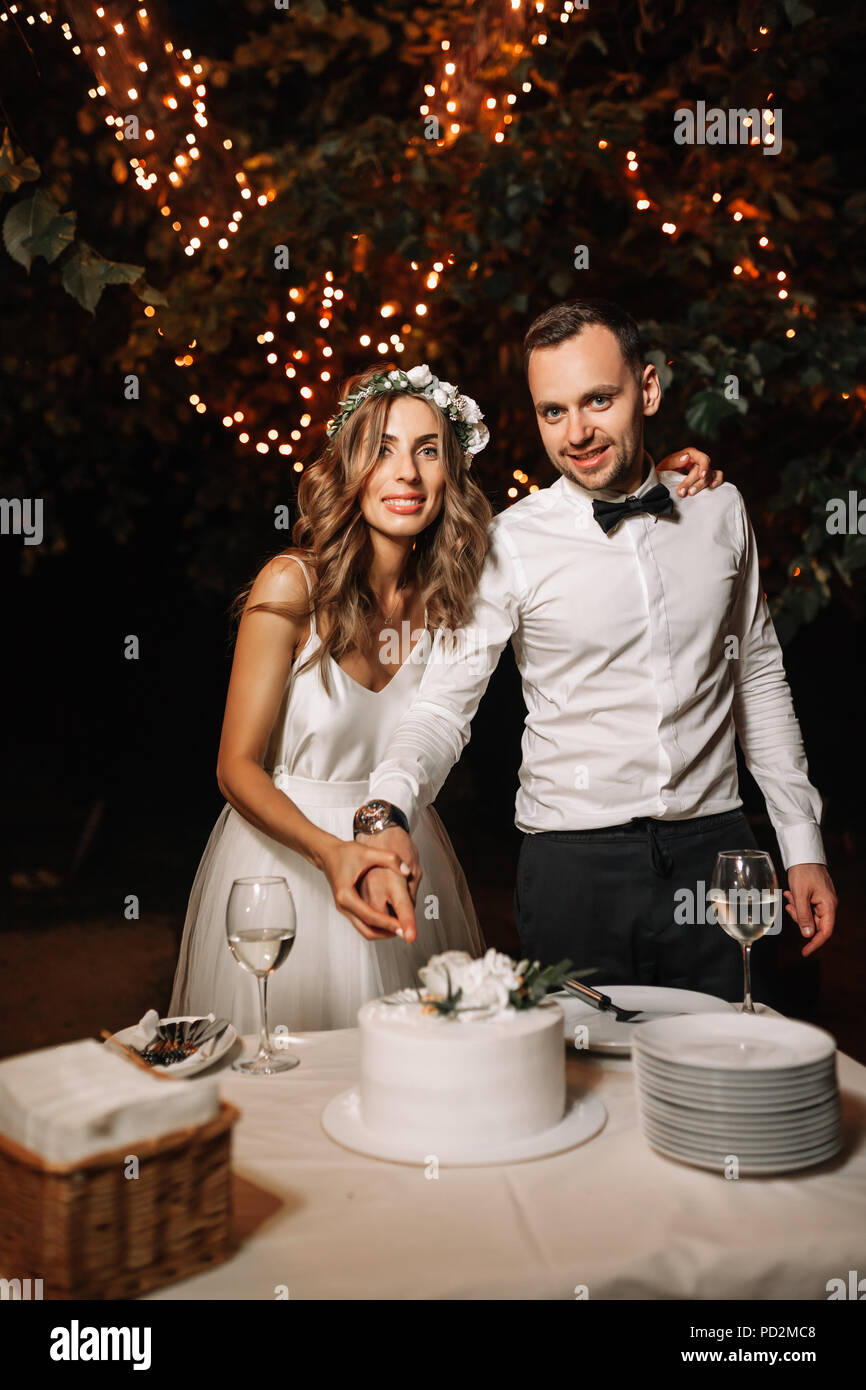 Happy Bride And Groom Cut The Wedding Cake In The Front Garland Light Decoration Wedding Evening Outdoor Sweet Happy Life Concept Stock Photo Alamy