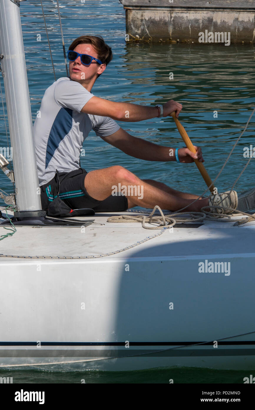 a competitor in the annual lendy cowes week regatta on the isle of wight paddling his yacht or sailing boat in light airs or no wind. - Stock Image