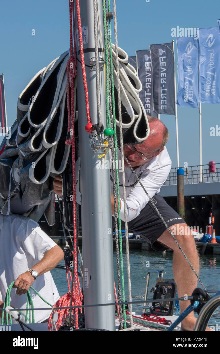 a crew member making ropes fast at the base of a mast and preparing a racing yacht  before going sailing during lendy cowes week regatta. - Stock Image