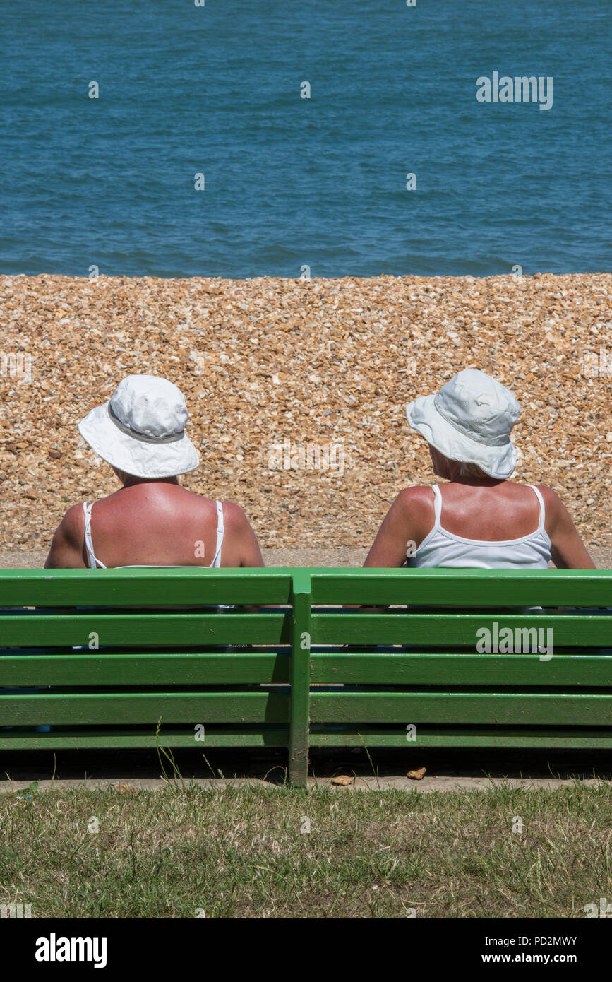 tow older ladies or friends sitting on a green painted wooden bench wearing sun hats sunbathing in the hot summer weather heatwave. retirement in sun. - Stock Image