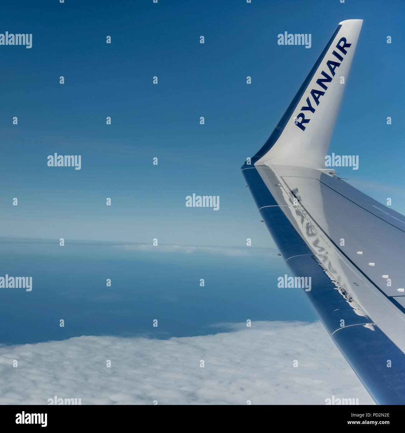 Ryanair, budget airline, Boeing 737 airplane flying in the blue sky. Wing with logo on winglet. Copy space. - Stock Image