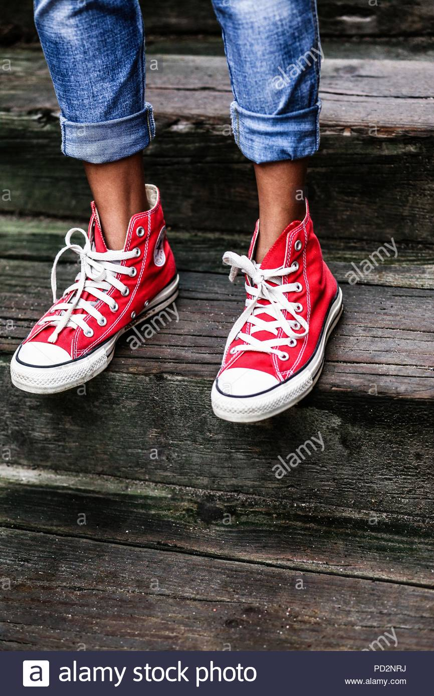 e389ee937a20 Legs and feet with red Converse sneakers Stock Photo  214575974 - Alamy