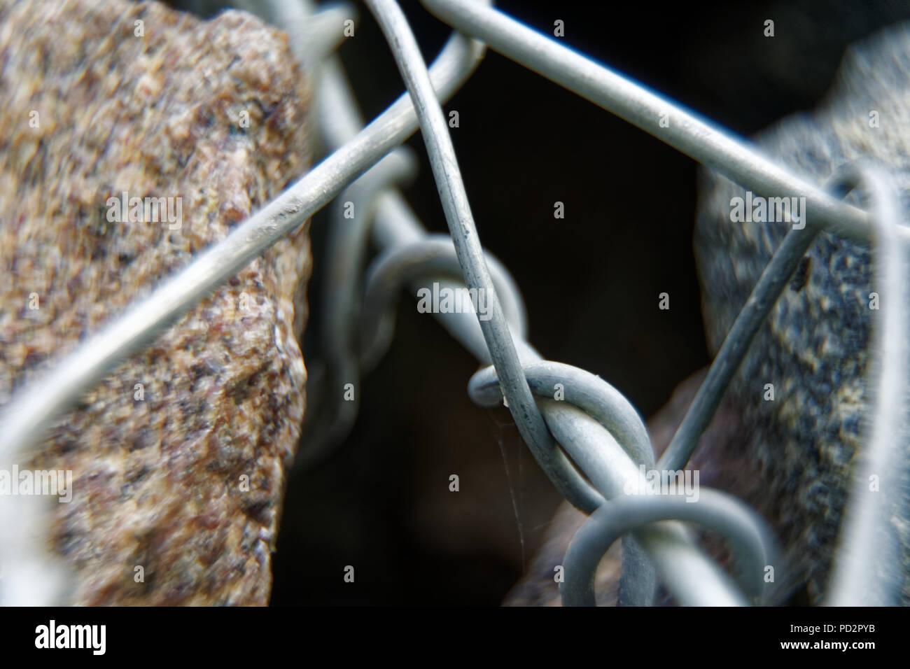 Aluminum wire twisted on stone object, macro background. - Stock Image