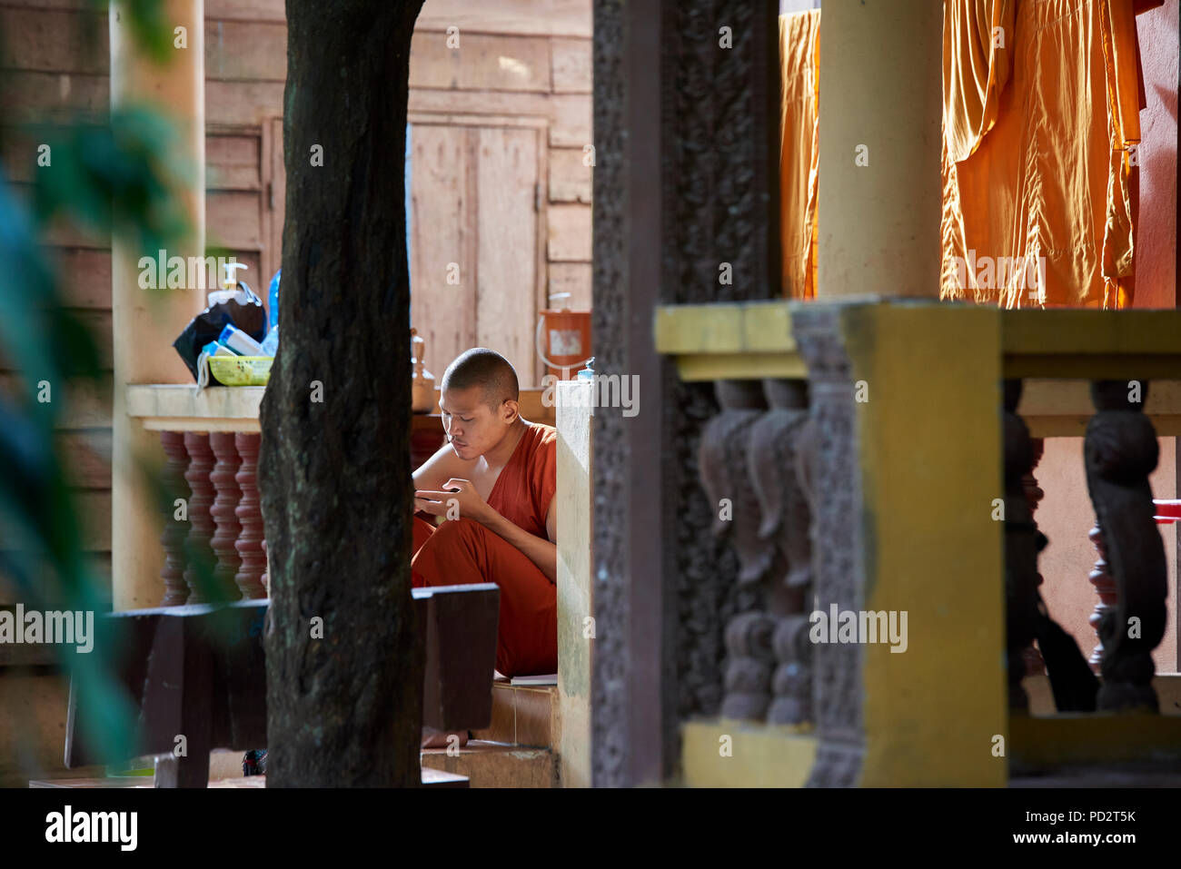 A young Buddhist monk relaxes in the sun near his drying robes. In Siem Reap, Cambodia. - Stock Image